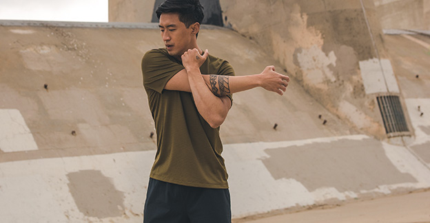 Man stretching in Saucony apparel.