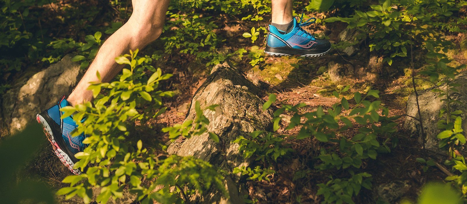Mens feet running thru the woods with blue Mad River TR shoes on.
