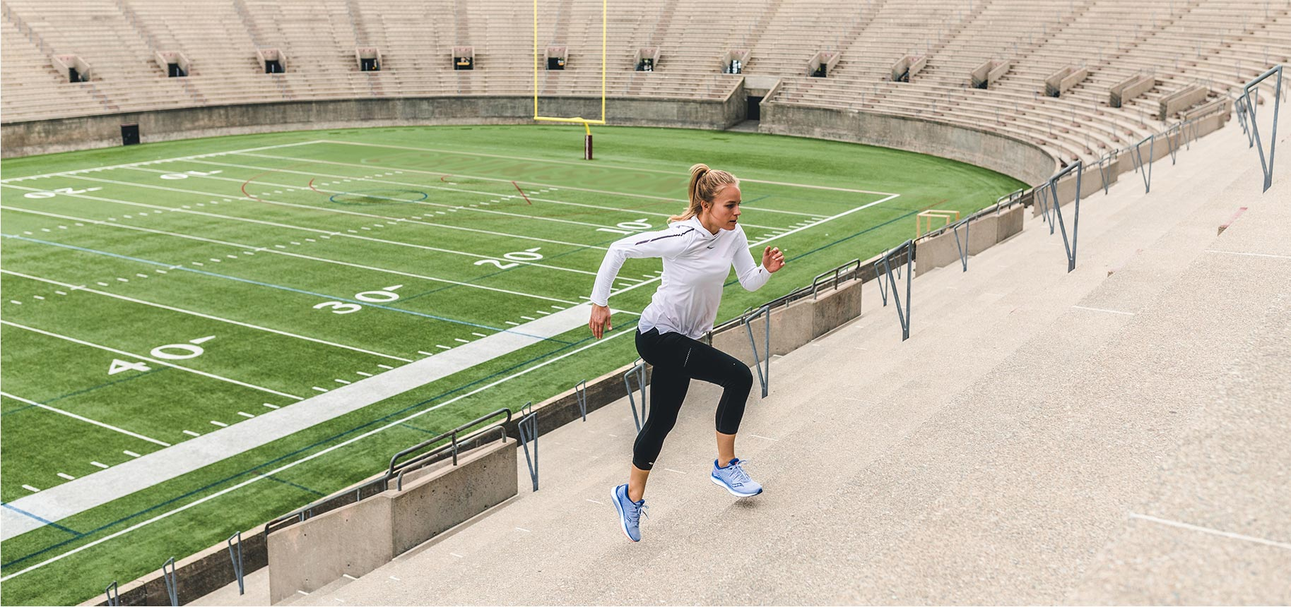 Daisy Robinton running in blue Saucony shoes up concrete stadium stairs with a football field in the background.