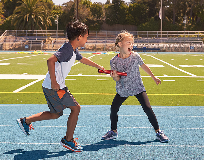 Kids exchanging a relay baton on a running track.