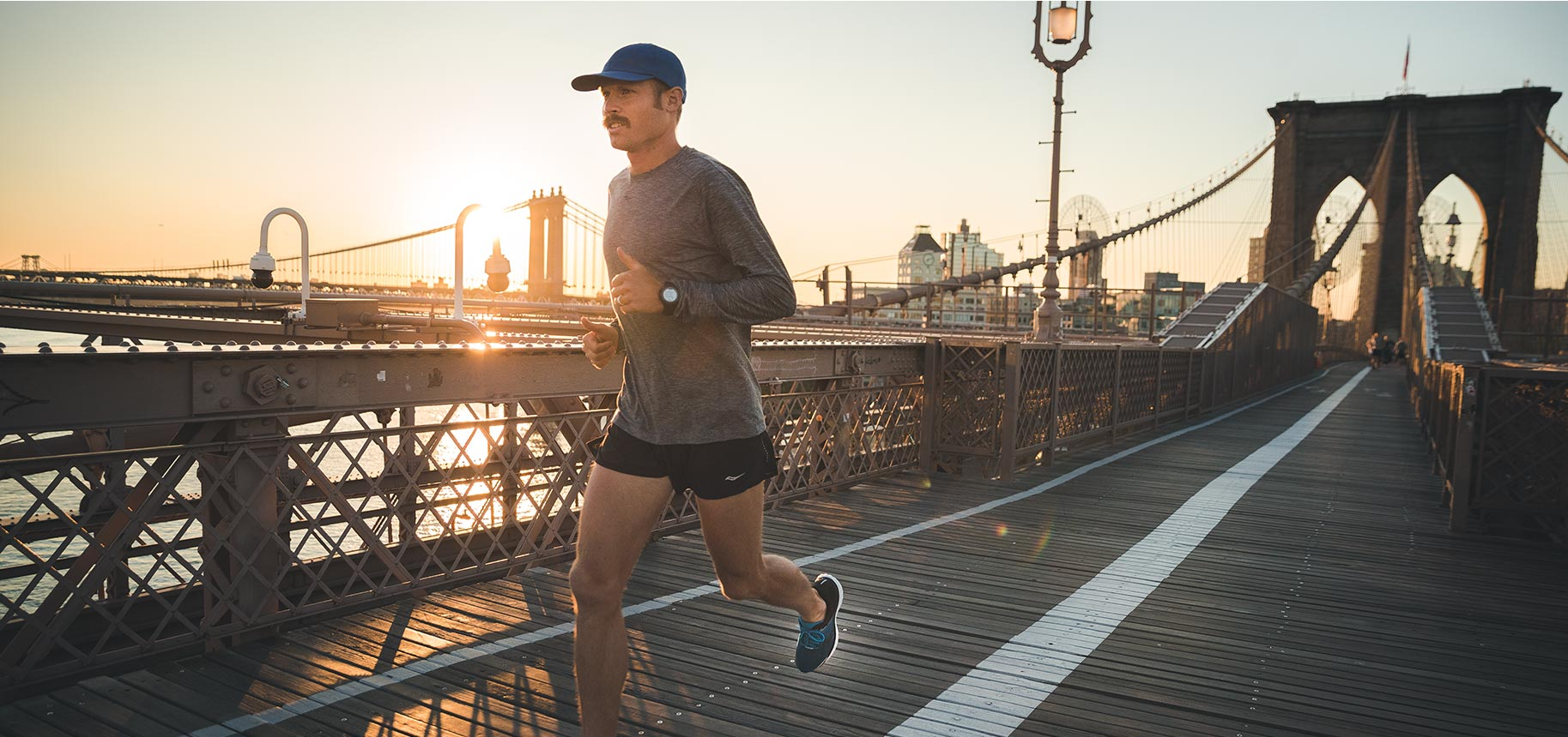 Jared Ward running on a bridge with the city skyline in the background.