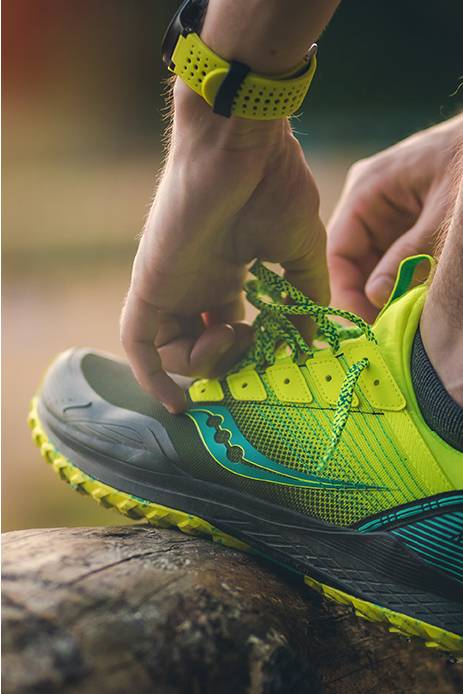 Closeup of Mad River shoe in green getting laced up