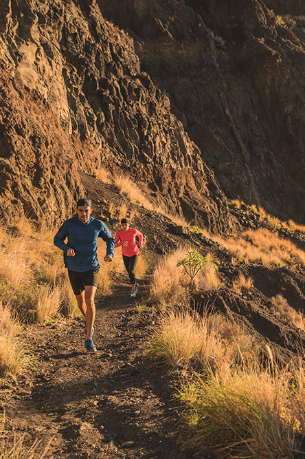 Man and woman running on a mountain track