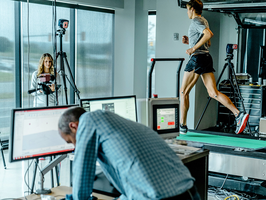 Runner on a treadmill being observed in a lab while testing out Saucony shoes.