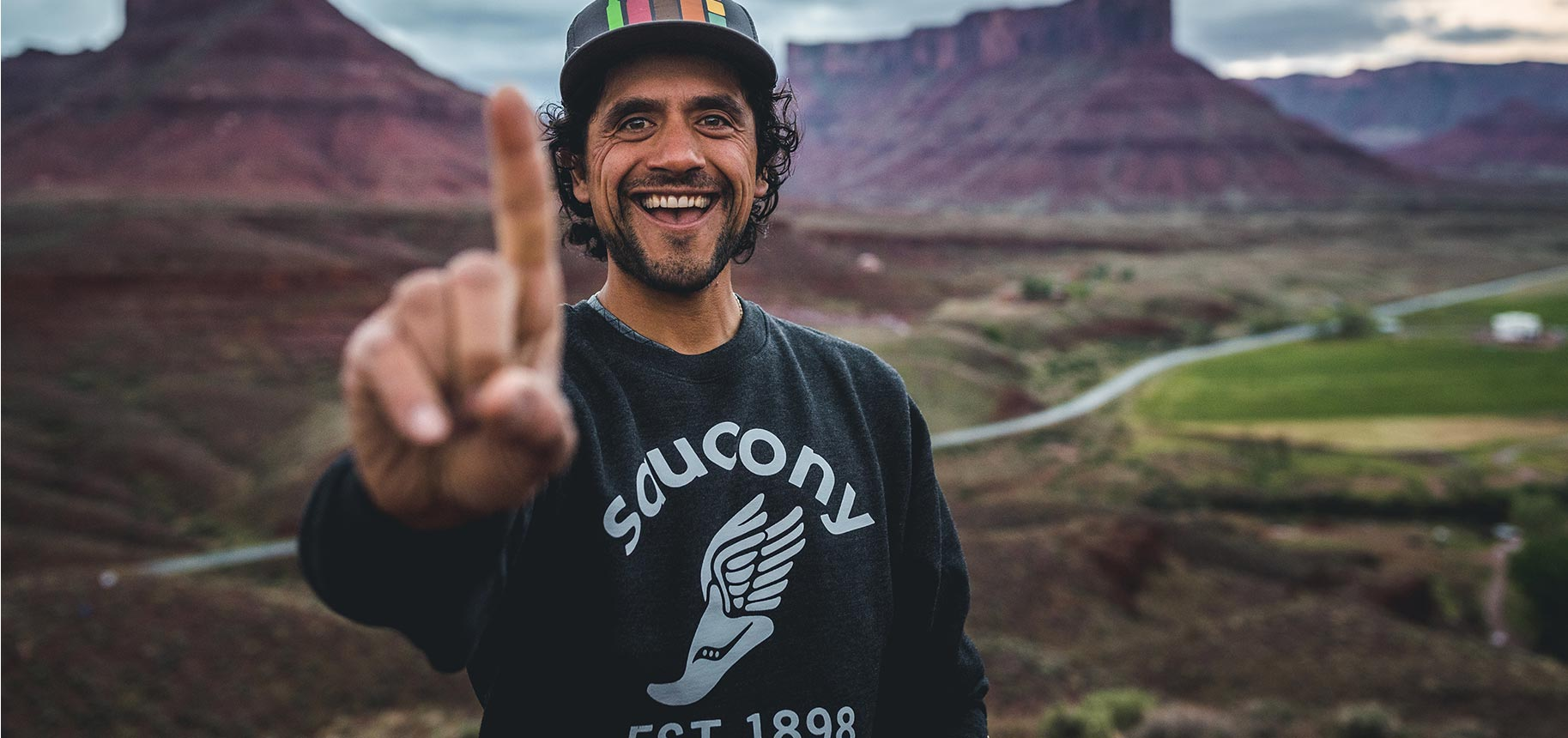 Eduardo Garcia's smiling face in a rainbow hat and Saucony EST 1898 sweatshirt showing his index finger as number 1.