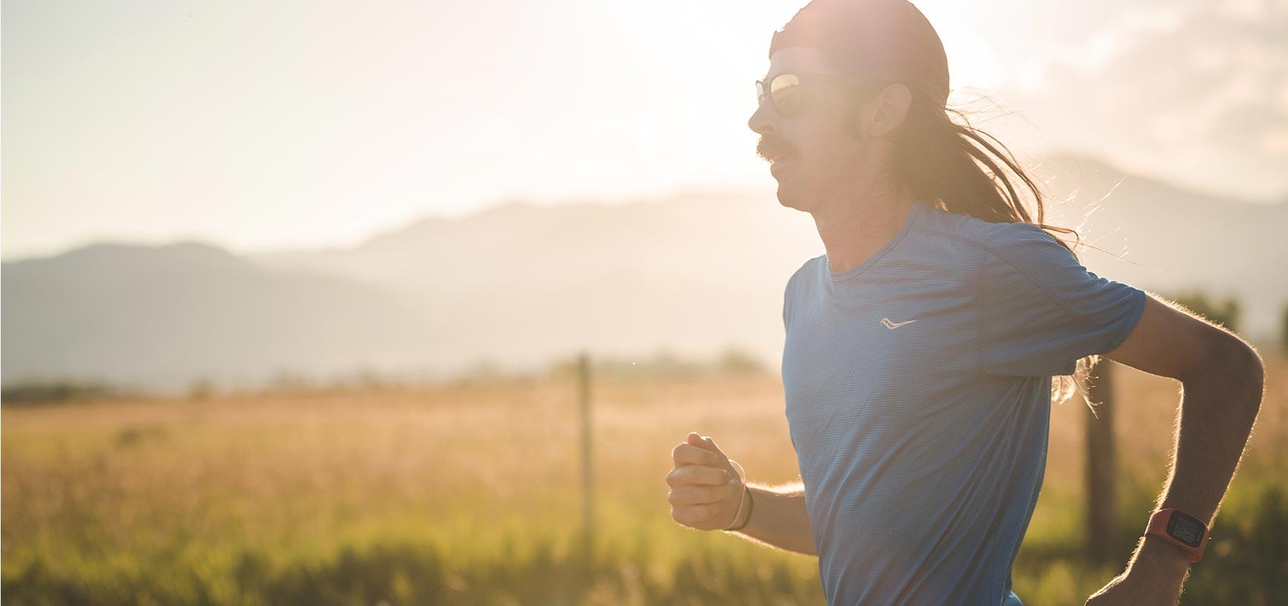 Noah Droddy running wearing a blue Saucony shirt with the sun gazing behind him.