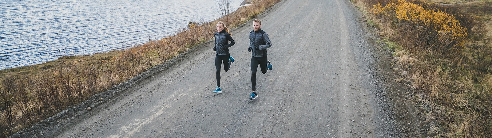 A male and female running on a dirt road next to a body of water.