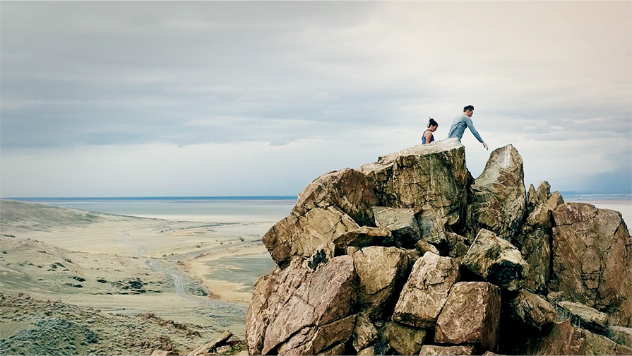 Video poster for Xodus ISO 3 promo video. Two people hiking on a rocky terrain.