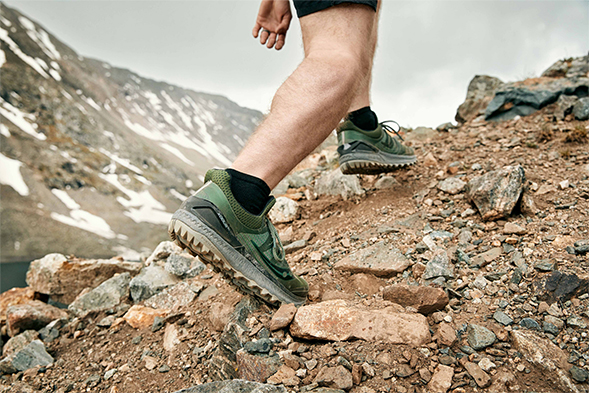 A shot of green Xodus ISO 3s in use. Wearer is climbing up a rocky dirt hill.