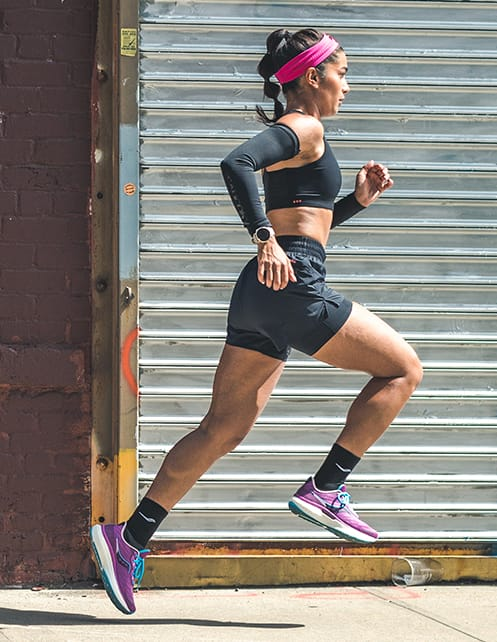 Woman running wearing Saucony Triumph 19 shoes.