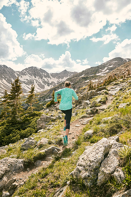 Woman running up a grassy mountainside. Blue skies above, a mountain range and pine trees visible in the distance.