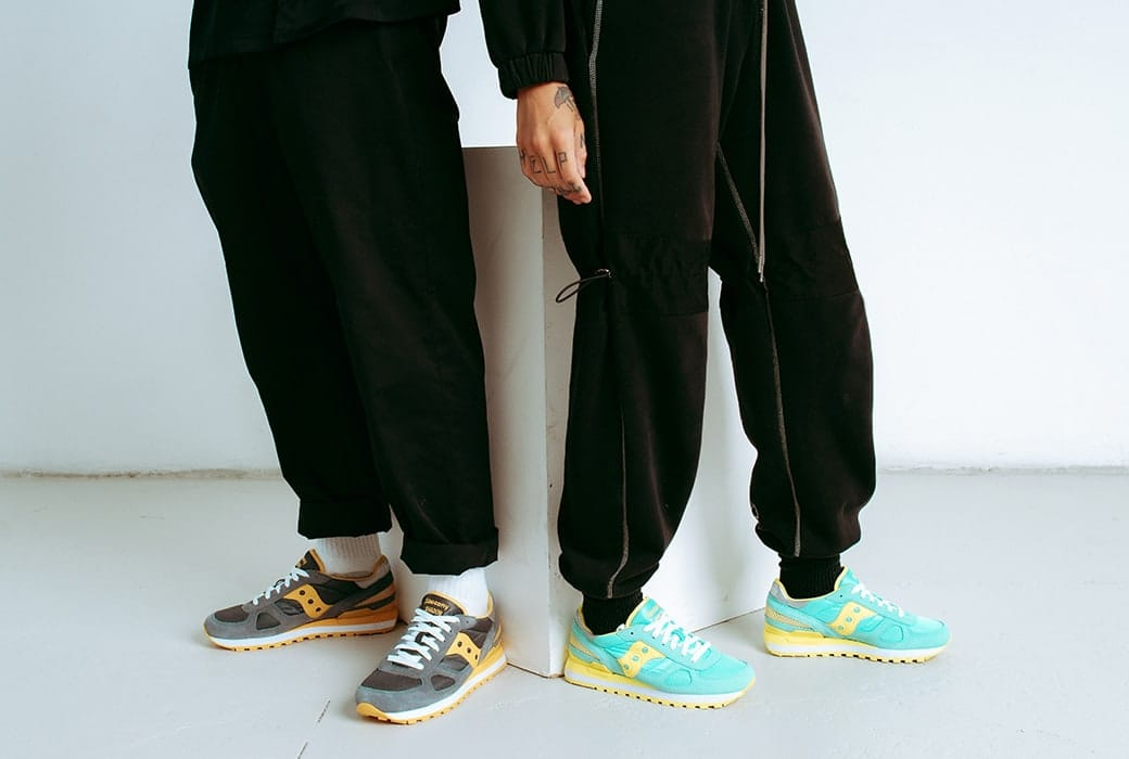 A close up of two people's feet wearing Saucony Shadow shoes.