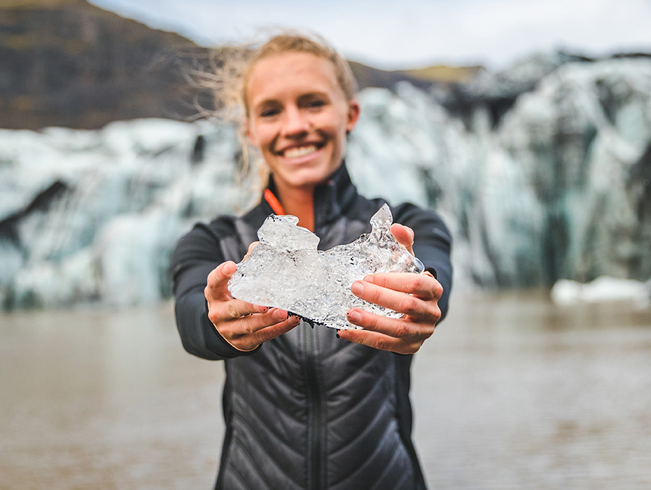 Female holds a piece of ice while standing in front of a glacier.