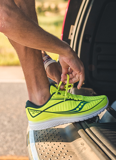 Lacing up a Kinvara 10 on the back bumper of a car.