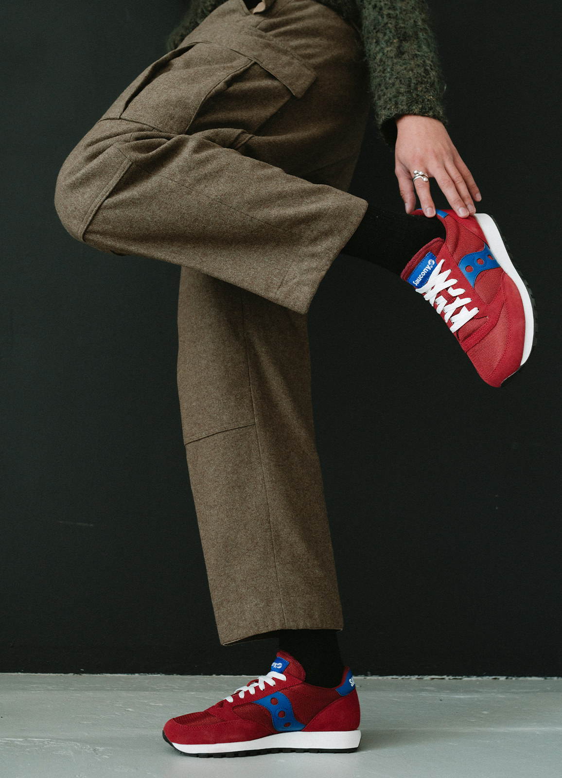 Person wearing wool pants and red Saucony Original Jazz shoes.