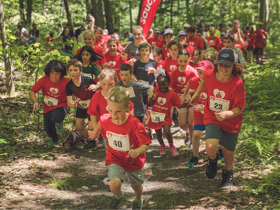 Pack of kids running down a wooded trail.
