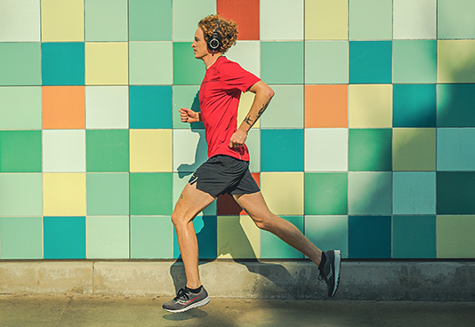 Person running with a colorful tiled wall behind them.