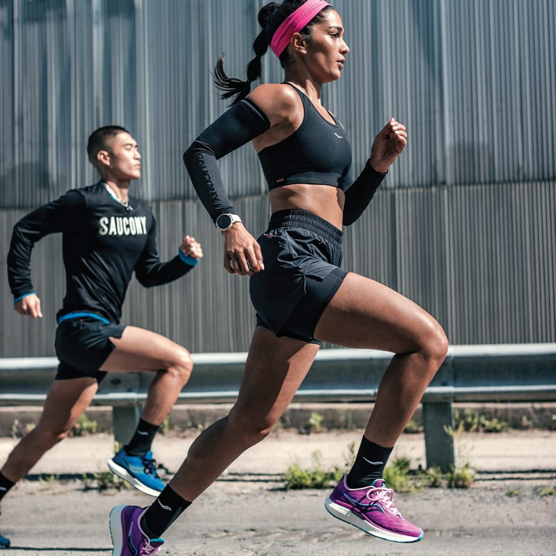 A man and woman running on the street.