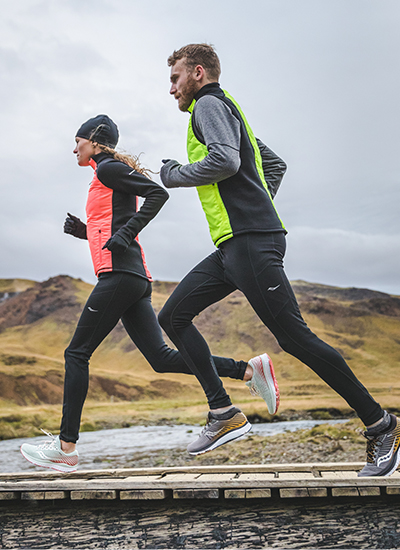 Two people wearing Saucony apparel run over rainy fells.
