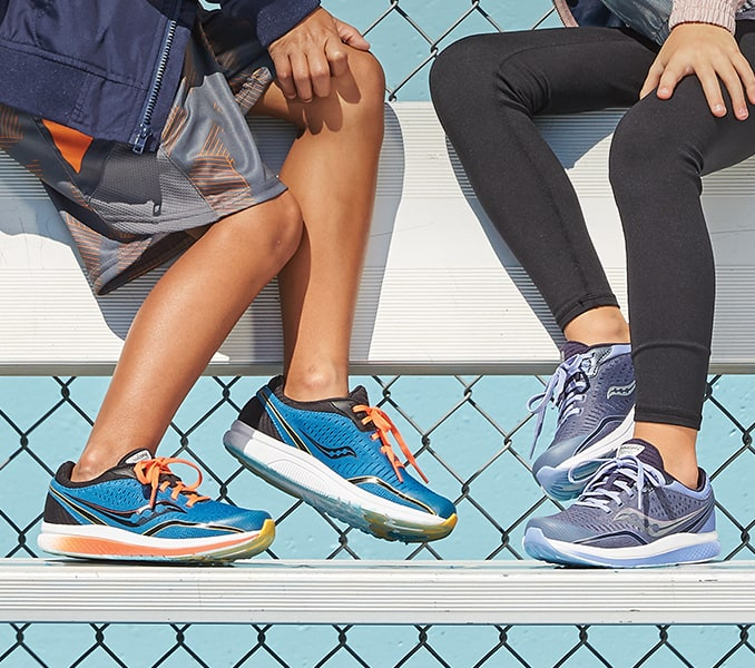 Two kids sitting on a bench, wearing Saucony Kinvara running shoes.