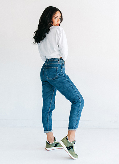Woman posing in Saucony Jazz Original Shoes and denim jeans.