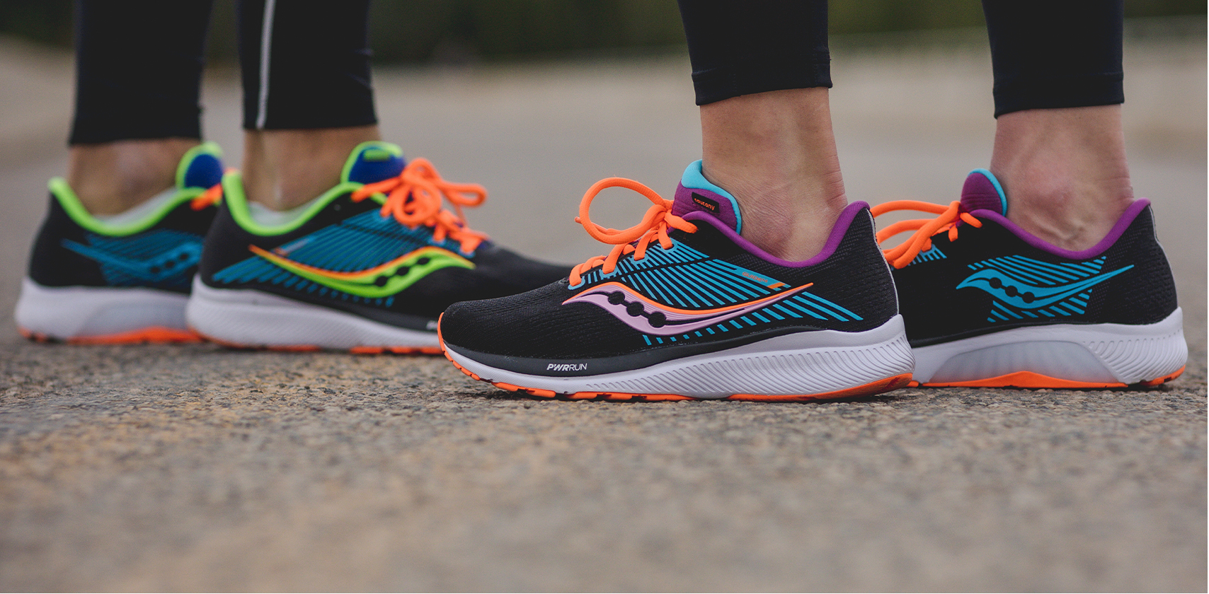 2 people standing with Saucony shoes and running pants.