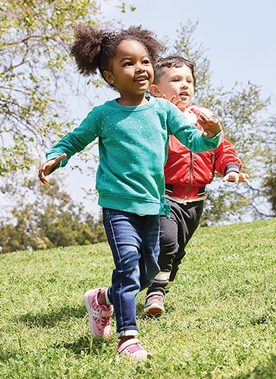 Two little kids running in the grass