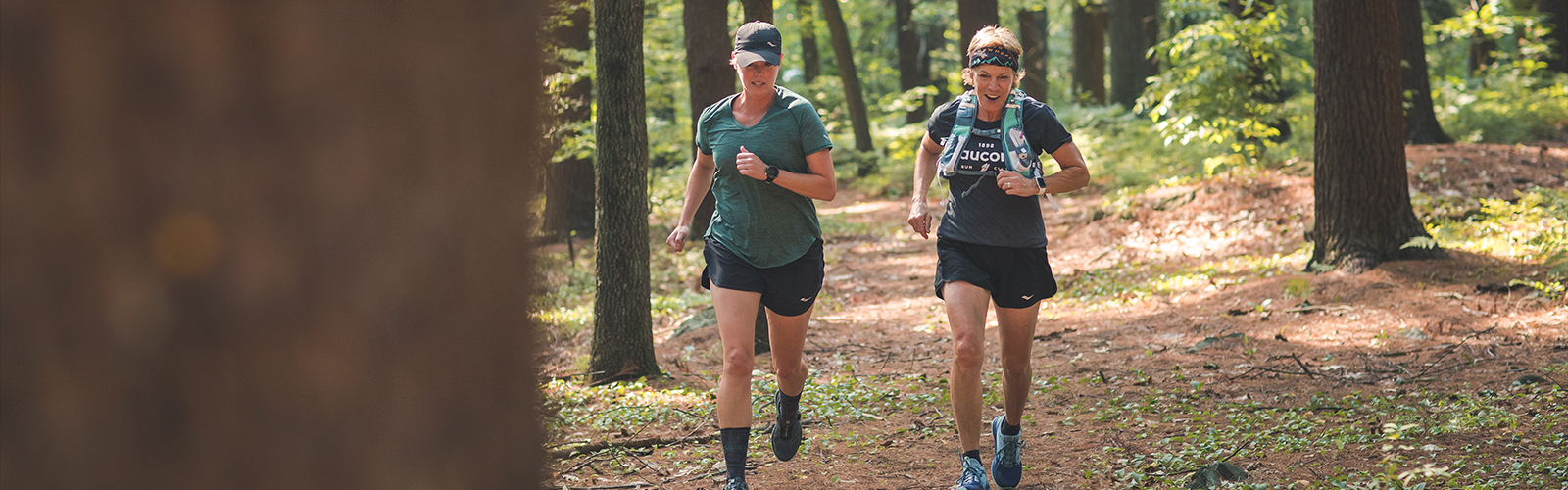 Two female runners enjoying a run on a forested trail.