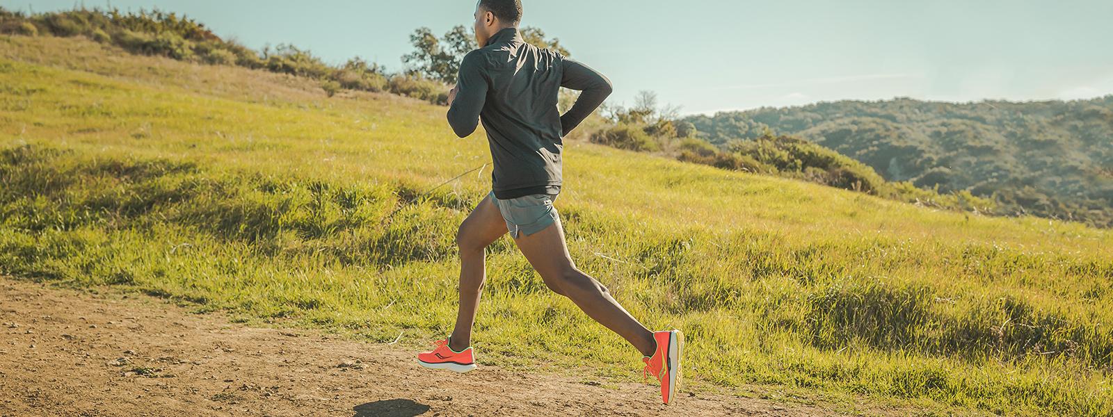 Runner climbs a hill.