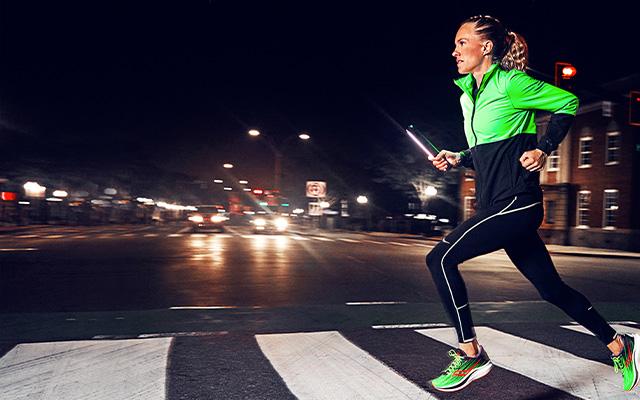 Running over a crosswalk at night wearing bright apparel.