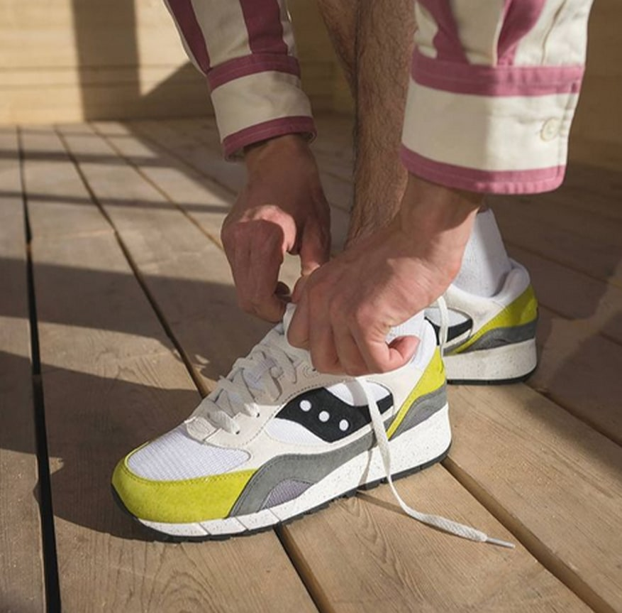 Person lacing up fresh Saucony kicks with yellow and grey highlights.