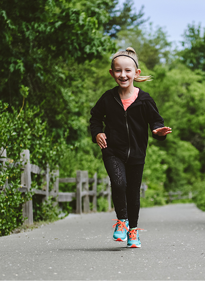 A happy little girl jogging in her Kinvara 11's.