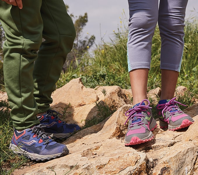Two kids on hike, standing on a rock, wearing Saucony Peregrine running shoes