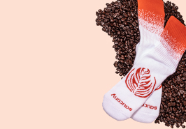 White socks with orange elastic and a pumpkin logo on the foot and the Saucony name embroidered on the toes.  Sitting on a pile of roasted coffee beans.