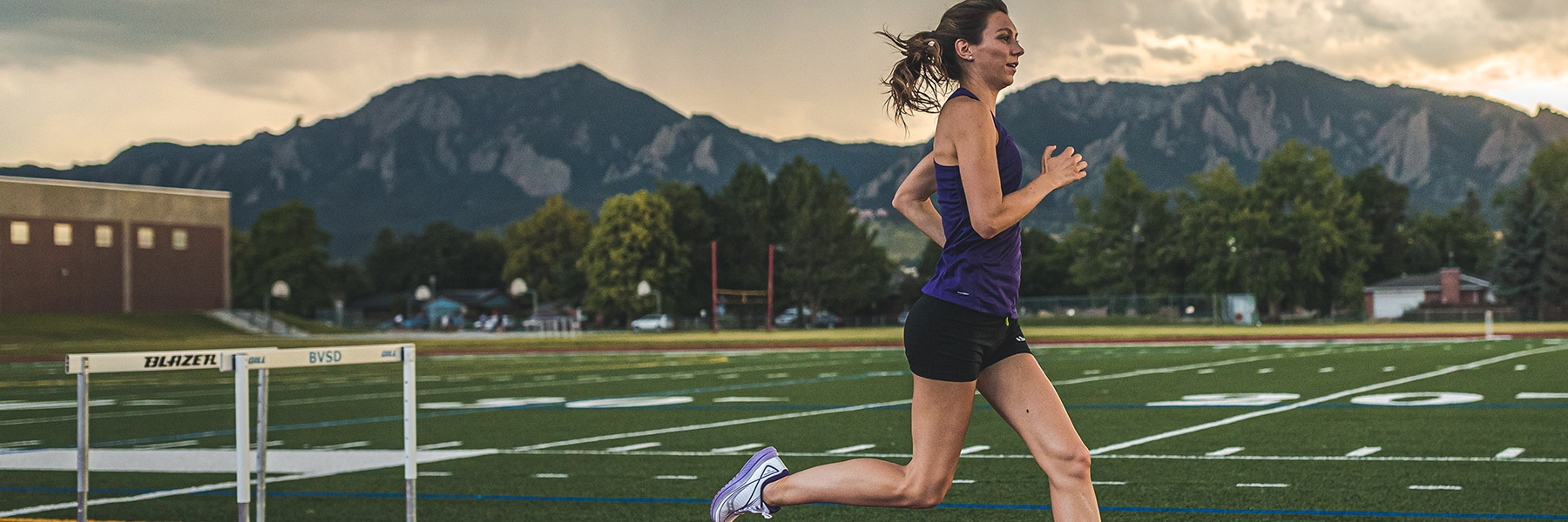 Woman training on a track with mountains in the background