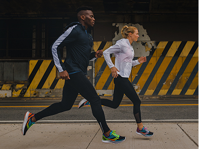 A male and female running downtown.