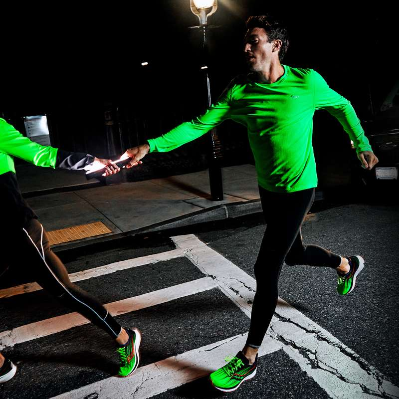 A man running in brightly reflective shirt and running shoes
