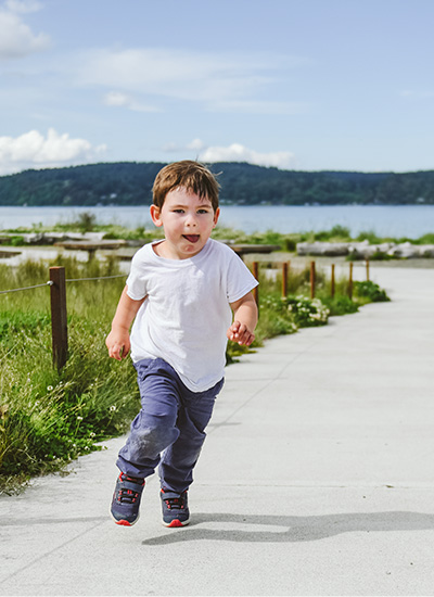 Kid running and playing in Saucony shoes