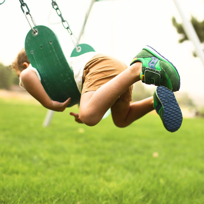 Young kid doing the superman on a swing.