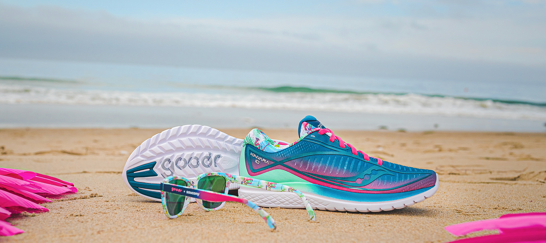 Blue and pink Saucony Goodr shoes on a beach with sunglasses casually sitting beside and bold pink flamingo feathers surrounding.