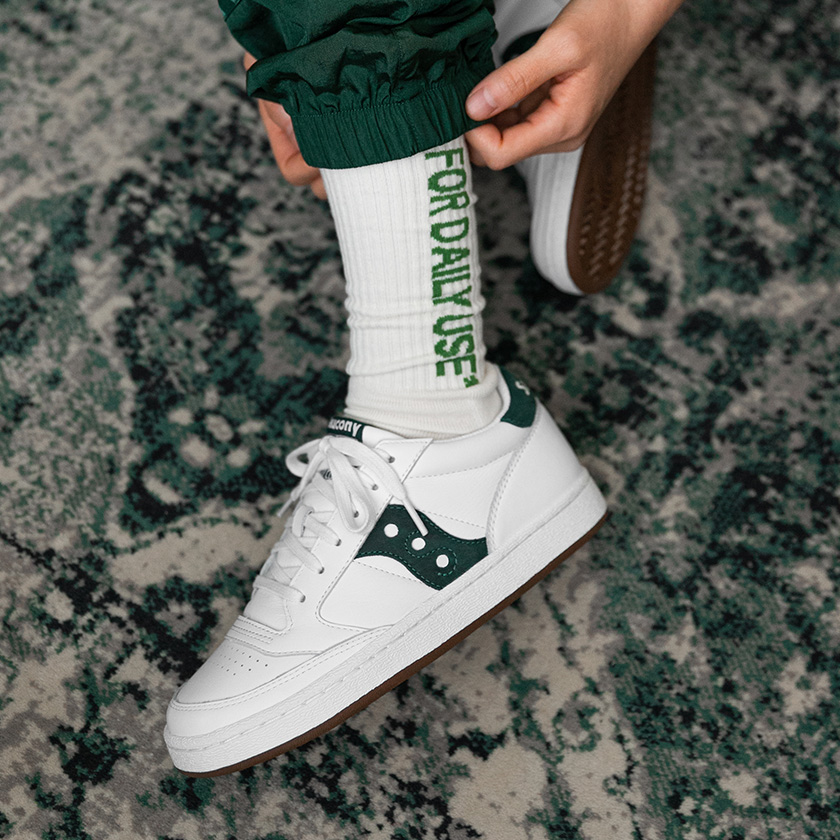 Green and white Jazz on a person wearing a green and white sock with a textured background.