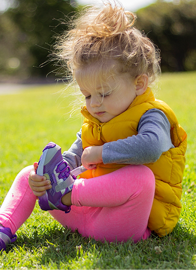 A kid sitting on the grass putting on their own shoes.