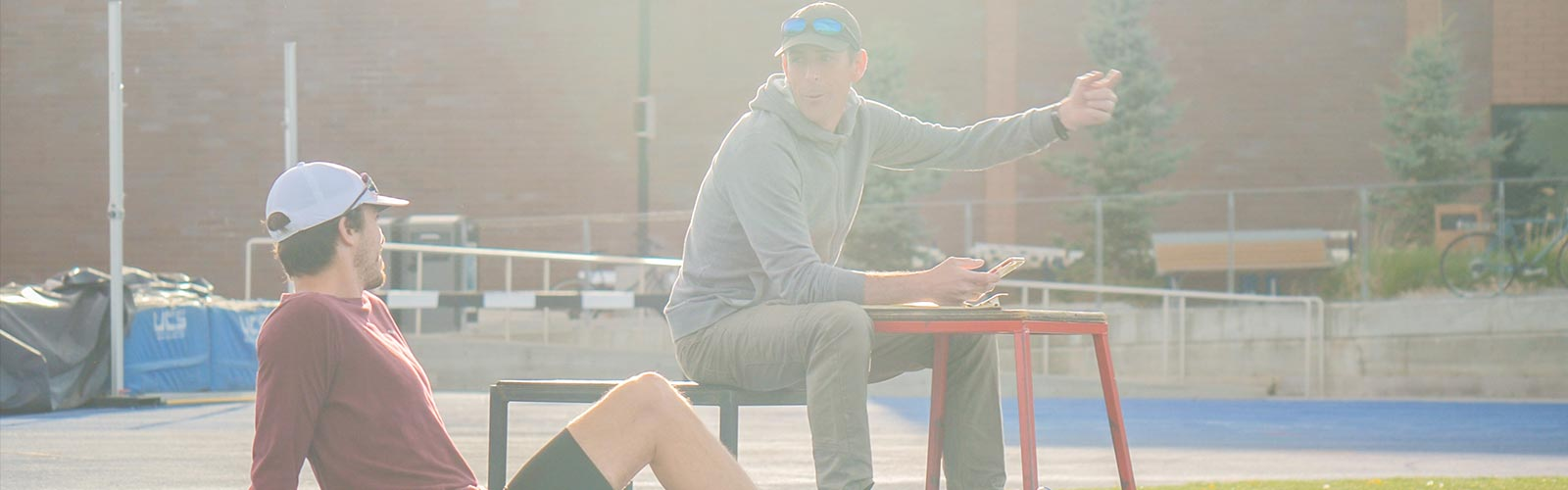 Track Club Coach Tim Broe giving tips sitting on a bench to a fellow runner.