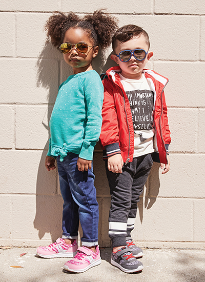 Boy and girl wearing sunglasses and Saucony shoes.