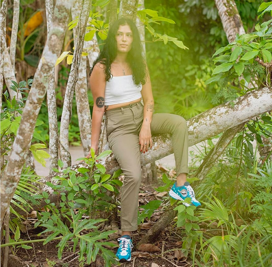 A girl taking a rest on a tree, wearing Saucony Originals.