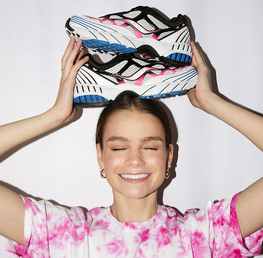 A girl balancing a pair of Saucony's on her head with her eyes closed and a big smile.