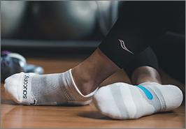 Someone wearing Saucony socks sits cross-legged on a wooden floor. Looks cozy.