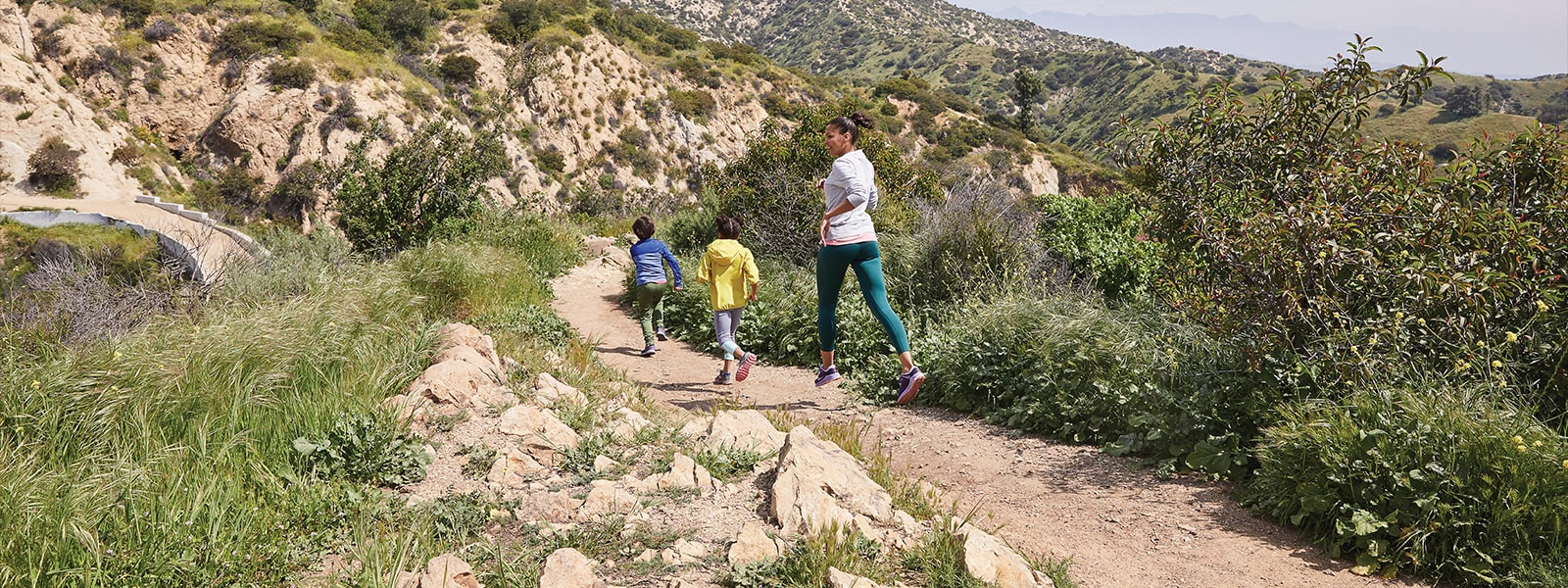 A mom and two kids going for a run on a trail