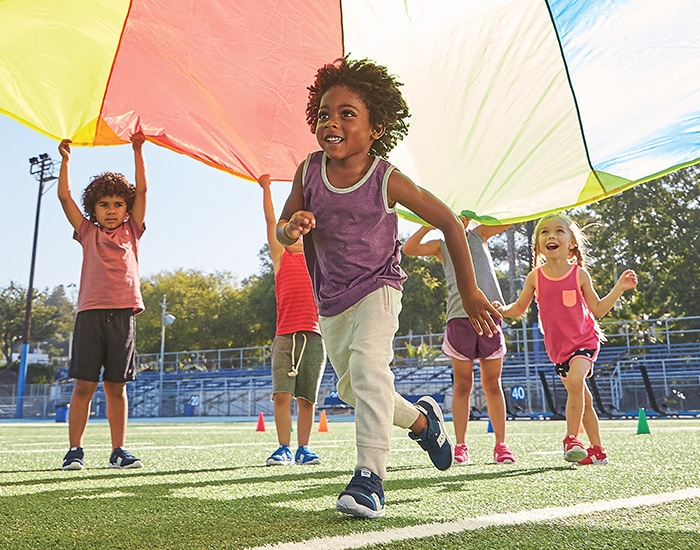 Kids running and playing on a football field, wearing Saucony Jazz Riff shoes.