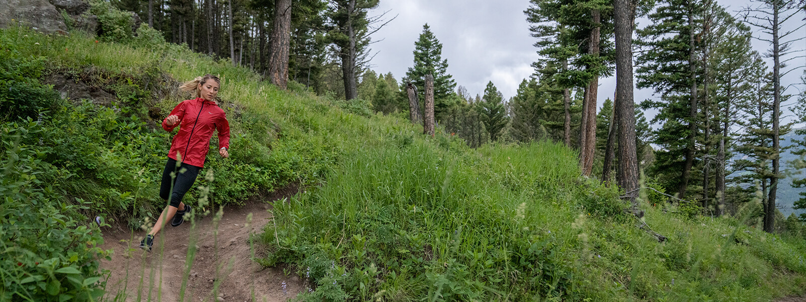 Runner hits a hairpin curve while coming down a dirt trail between trees on the side of a grassy mountain.